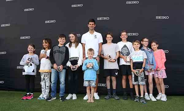 Novak Djokovic presents children with a special watch in honour of his Foundation.